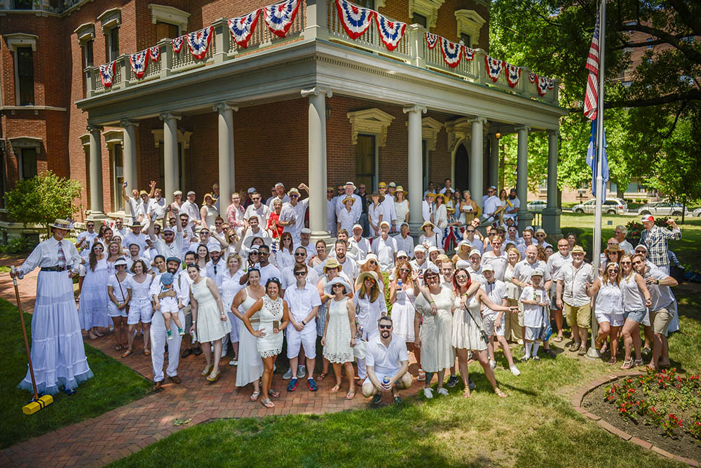 Photograph of a large crowd dressed in white in front of the Harrison mansion.