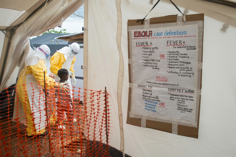 July 17, 2014. MSF staff show the way inside the treatment center to a patient most likely infected with the Ebola virus.