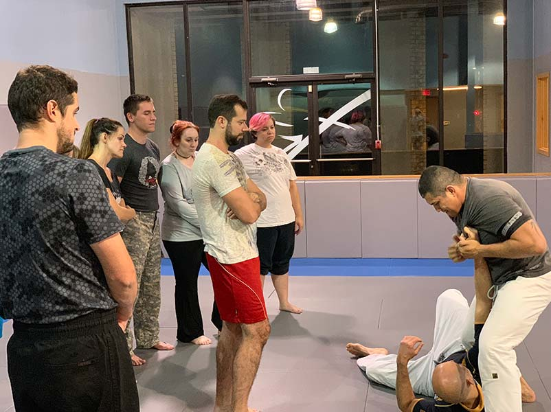 photo of coach Cris showing a lapel counter at journey jiu jitsu madison academy