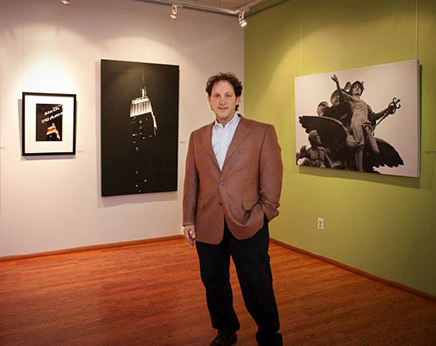 Andrew Darlow standing in front of a few of his prints during a solo show at Alfa Art Gallery
