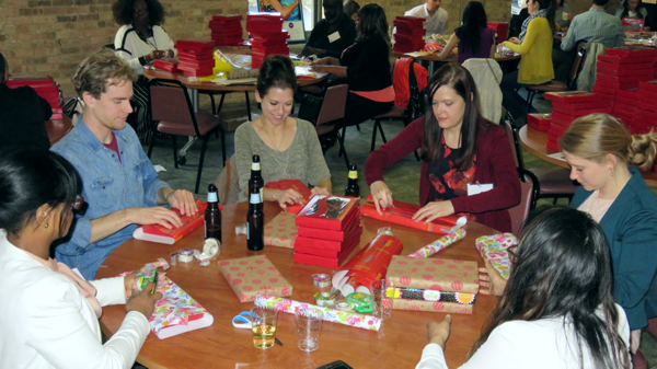 young professional volunteers come together to wrap gifts