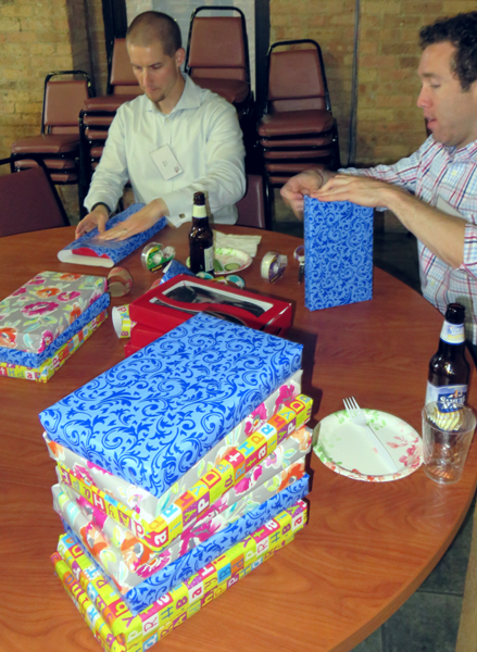 young professionals enjoy food, drink, and help wrap gifts
