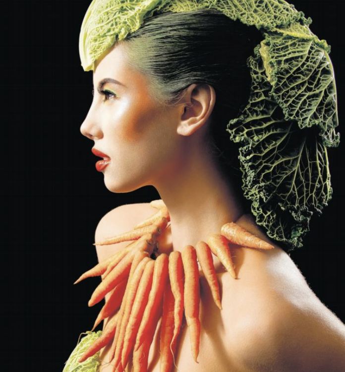 Model wearing a crown of cabbage leaves and a carrot necklace