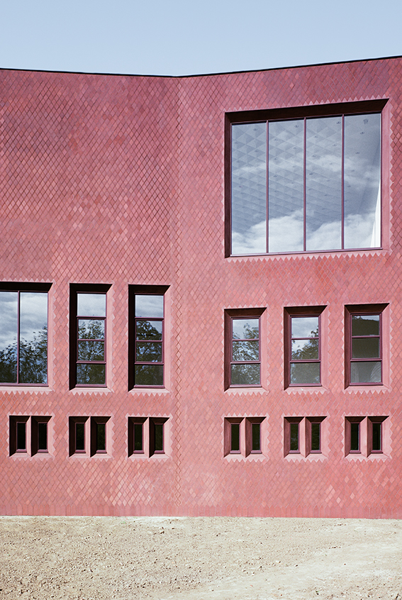 An elevational view of the brick facade of z33 by Torzo features assymetric openings and a pinkish hue of specialised brickwork in a diagonal pattern