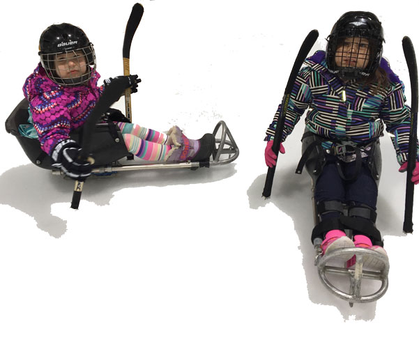 Two young girls play sledgehockey