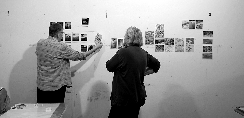 Doug+Vicky discuss photos on the studio wall
