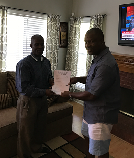 Grand Prize Winner-Elvis Momoh receiving his ticket voucher to Las Vegas