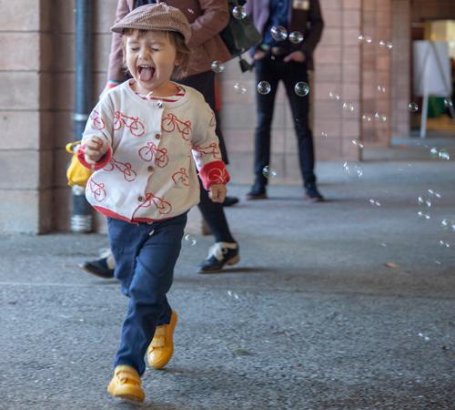 Kid running through bubbles