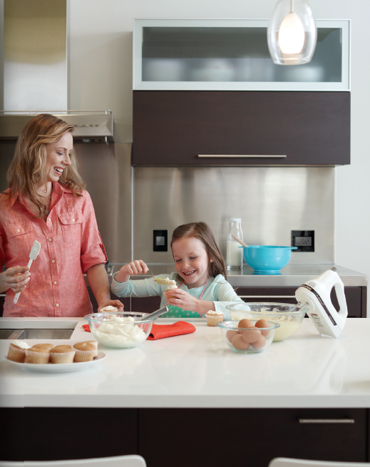 photo of kitchen with mother and child cooking together, legrand switchplates visible on wall behind