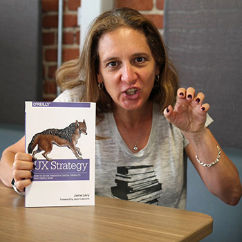 Jaime Levy posing as jackal with her book UX Strategy