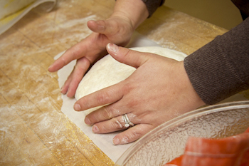 Using hands to shape sourdough bread