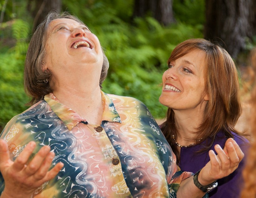 Two women, one arms open, joyous, the other witnessing