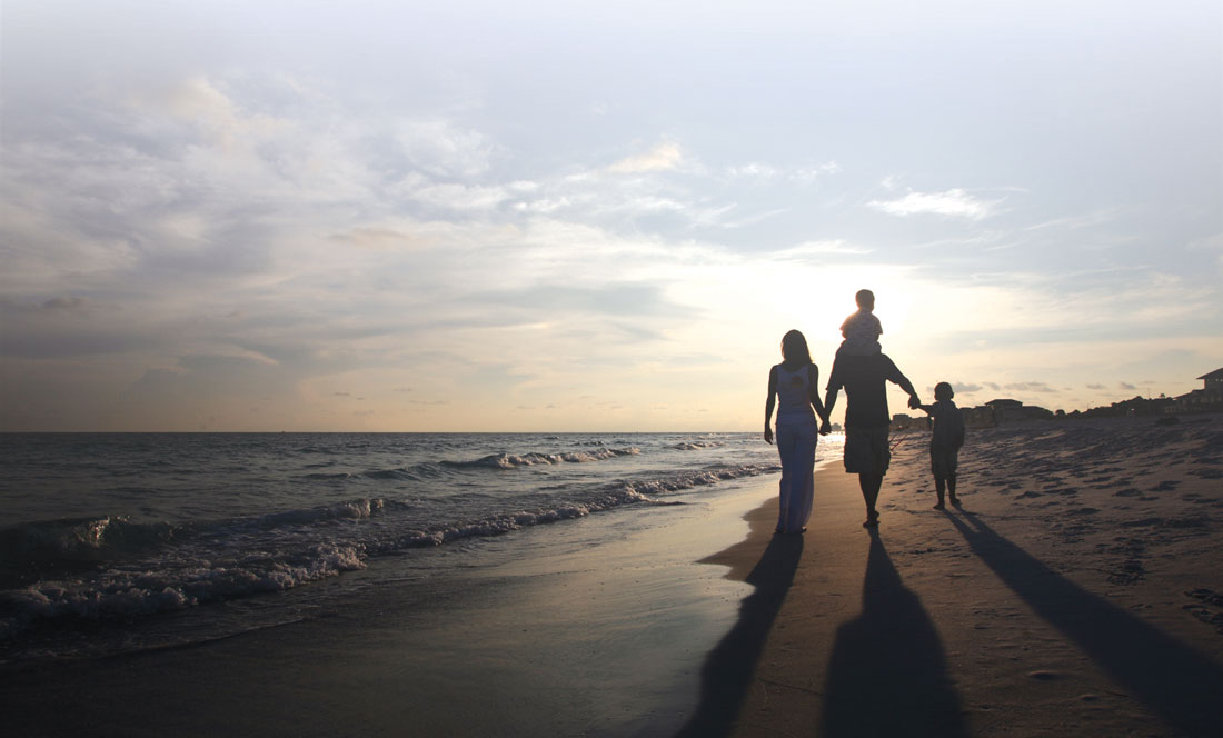 Family walking toward horizon on the beach