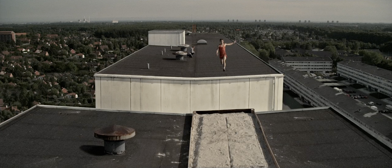 bird's eye view of a person jumping across rooftops
