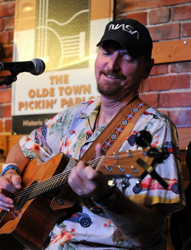 a goateed man with pulled back hair underneath a black NASA baseball cap looks loving at the acoustic guitar he is strumming. he is wearing a light buttoned up shirt with hawaiian print and flaming cars on it.