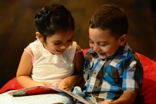 two children smile over an open book