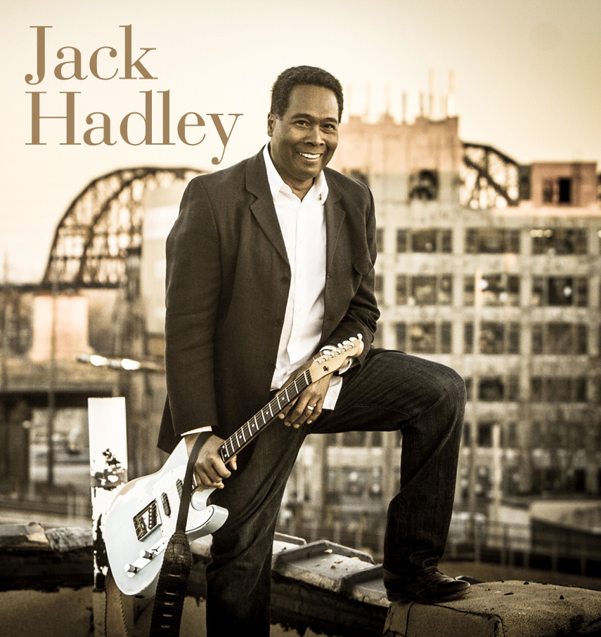 image of musician Jack Hadley smiling and holding a guitar
