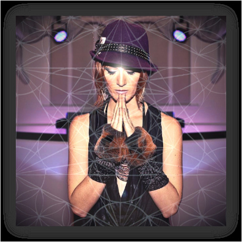 A woman in a purple studded had with her eye closed and her hands together as if praying just beneath her chin. She is wearing a tank top and arm cuffs, and the overall image is overlayed with a lattice design.