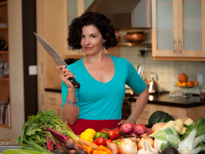 a woman with short brown hair with a blue shirt and her hand on her hip, hold a chopping knife before a layout of many fruits and veggies