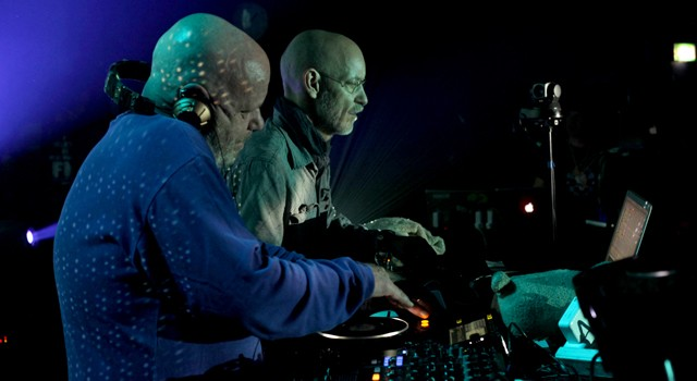 A view from behind two bald men hovering over computer screens and mixing boards on a stage before a huge group of dancing people