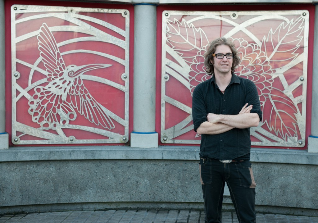 Man with long hair standing in front of a wall with steel cut artwork of leaves and a humming bird