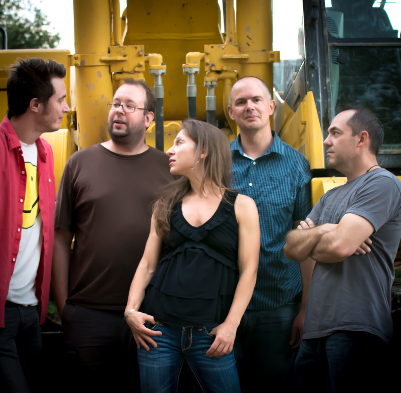 a band of five people stand in front of a yellow industrial looking background. all but one of the members is looking away from the camera.