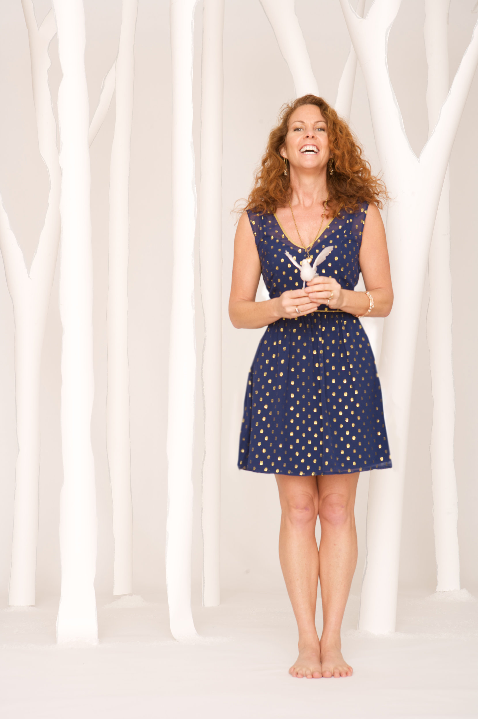 a woman stands to the right of the image, in front of a backdrop of light gray and white tree silhouettes. she is barefoot, wearing a navy blue dress with yellow polka dots and a cinched waist. her hair is curly, long, and parted to the side. she is holding a fake white bird and laughing joyfully.