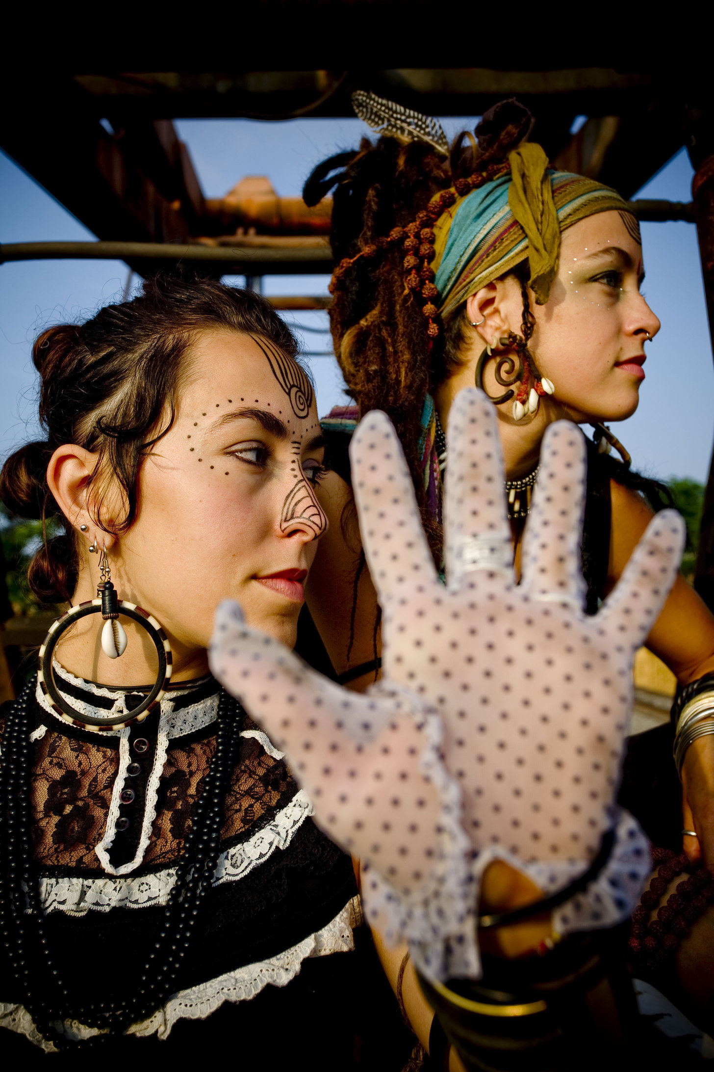 two decorated women sit in an open vehicle and are looking away to their left from the camera. the woman in the foreground has small decorative face paint surrounding her eyes, and the other woman is wearing a scarf around her dreaded hair. the woman in the front has her hand up, full palm to the viewer, in a lilac lace glove.