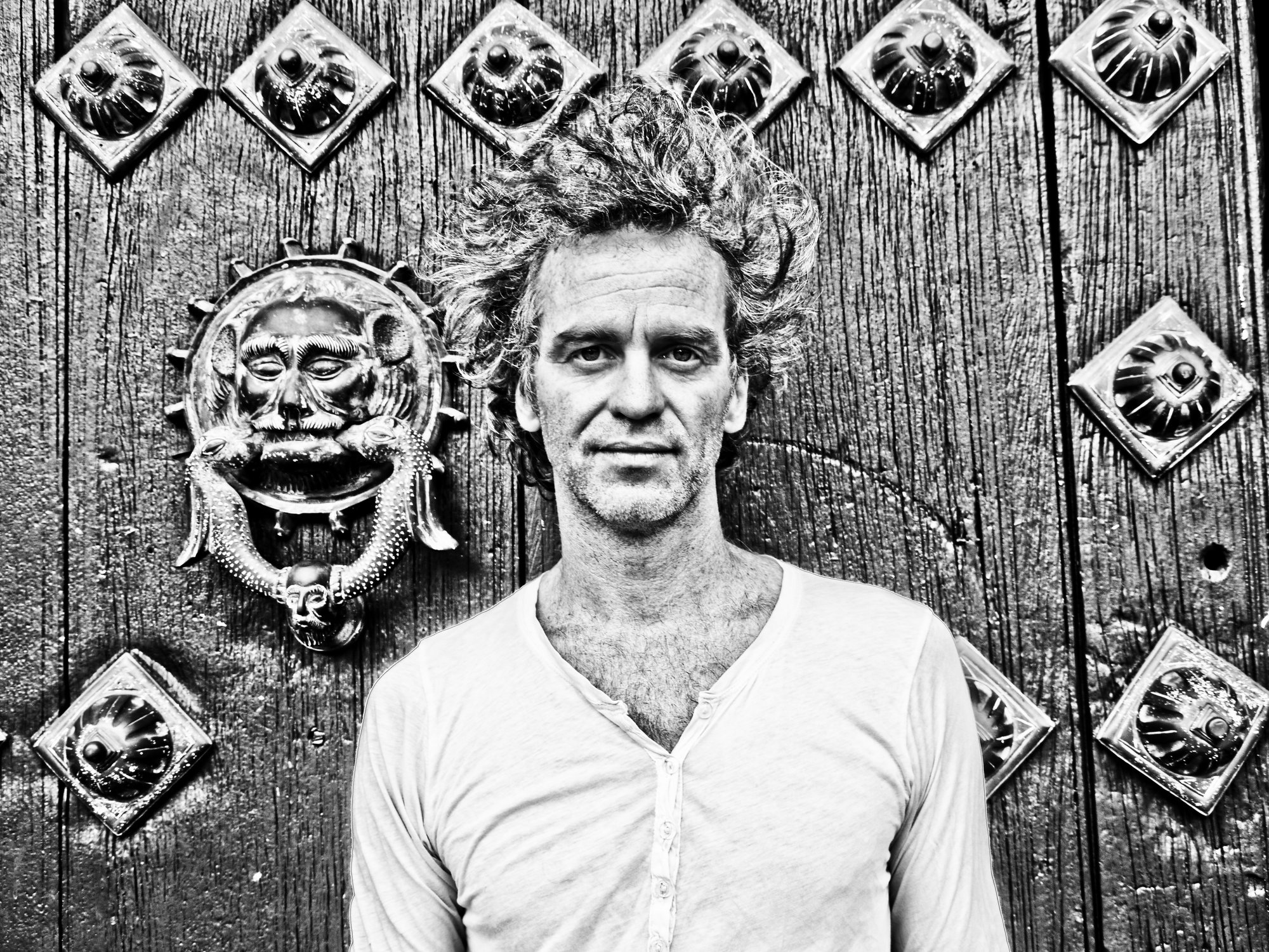 a black and white image of a wild haired man with a v-necked white shirt face the viewer on a backgrop of an ornate carved door