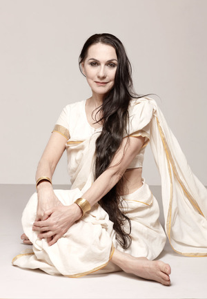 a yogini in cream sit smiling delicately at the viewer with her legs entwined, her hand across her knees, and her long brown hair reaching to her hips