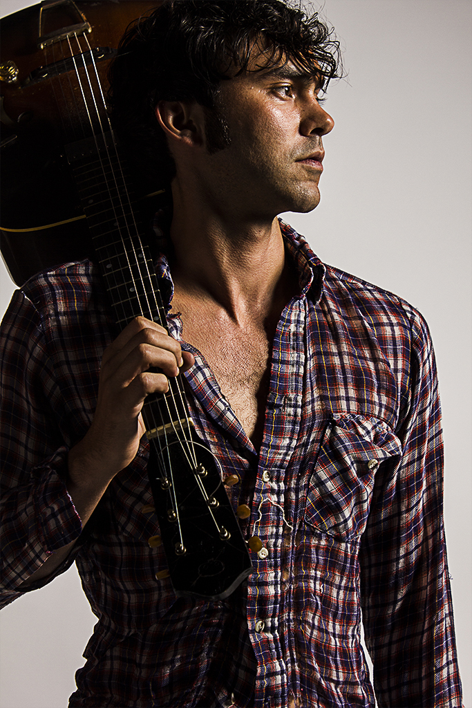 a dark featured man in a plaid shirt stands with a guitar slung over his right shoulder