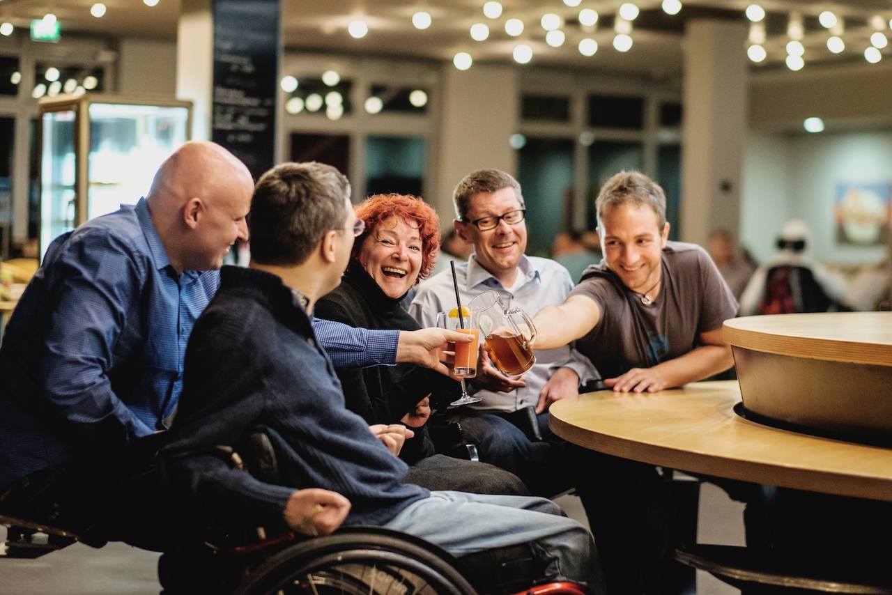 people in a bar, one using a wheelchair