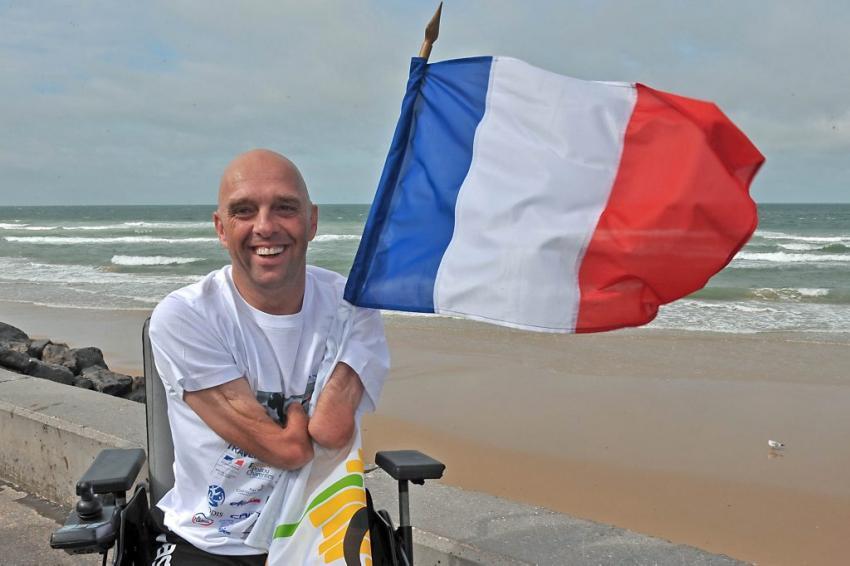 photo de Philippe Croizon devant la mer avec un drapeau de france