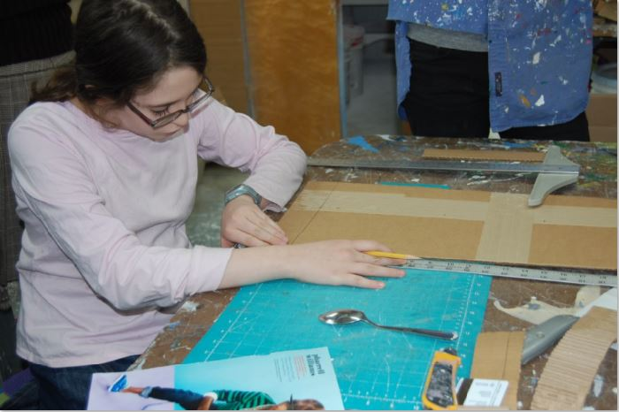 Young woman sitting at workbench, using a ruler to measure a piece of cardboard.