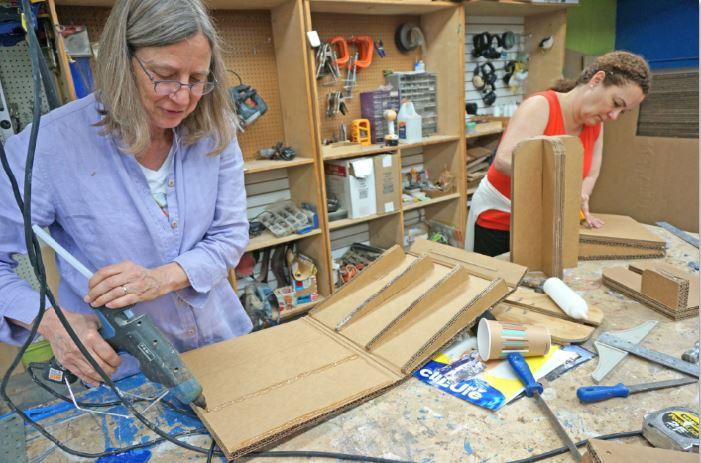Woman in workshop, using glue gun on a cardboard seat wedge.