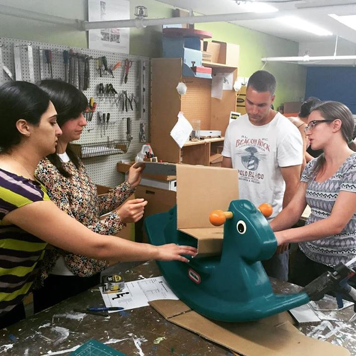 Four students designing an adaptation for a child's hobby horse.