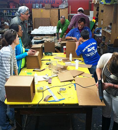 ADA's workshop.  Several people working with cardboard, while several others watch.