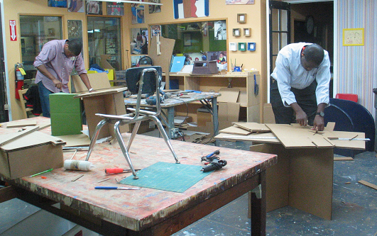 Workshop:  two men working at separate tables, using tools to work with cardboard