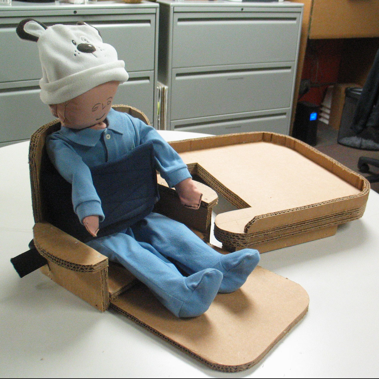 Toddler-sized doll in a cardboard seat