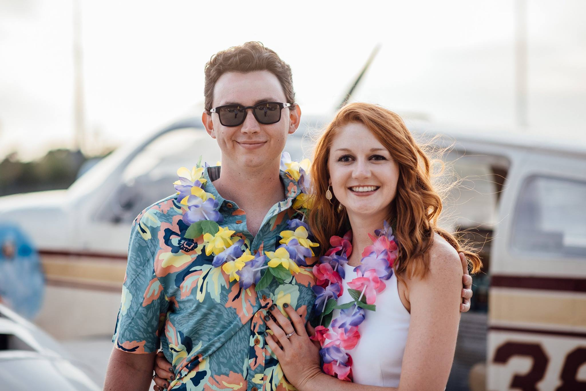 A couple with Hawaiian leis smiles for the photo