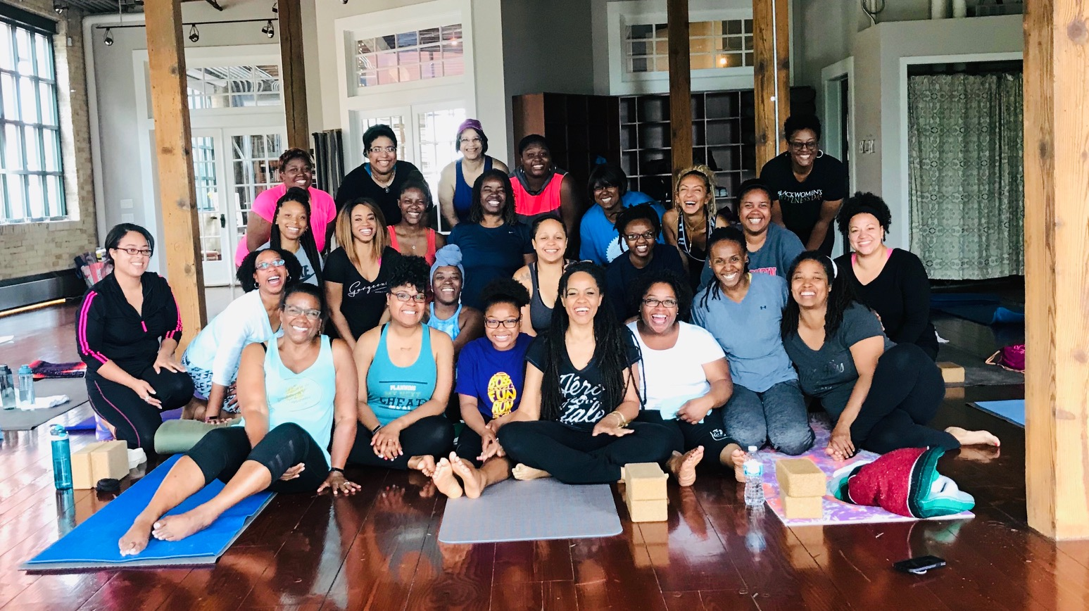 group of smiling women in yoga studio