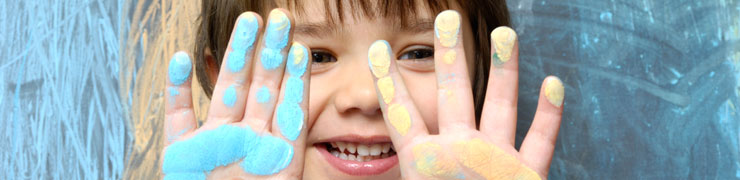 Smiling child with color on hands