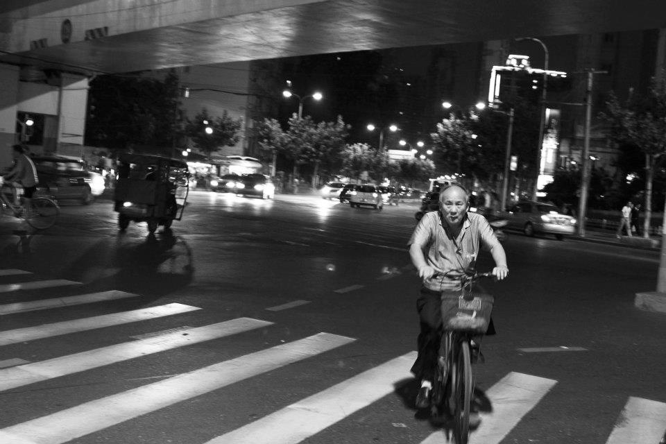 Every hour is rush hour in Shanghai—messy, disorganized, crowded, and beautiful. Bike riders crowd the city streets, even as Shanghai develops its public transportation routes. While Shanghai is now the symbol of China's present and future, it still maintains the ways of the past. Ironically, these new modes of transportation are contributing to the already desperate environmental situation in China, raising questions about whether modernization is actually improving the situation. Regardless, the city moves at its own convenience, hurrying along in its magical transgressions.