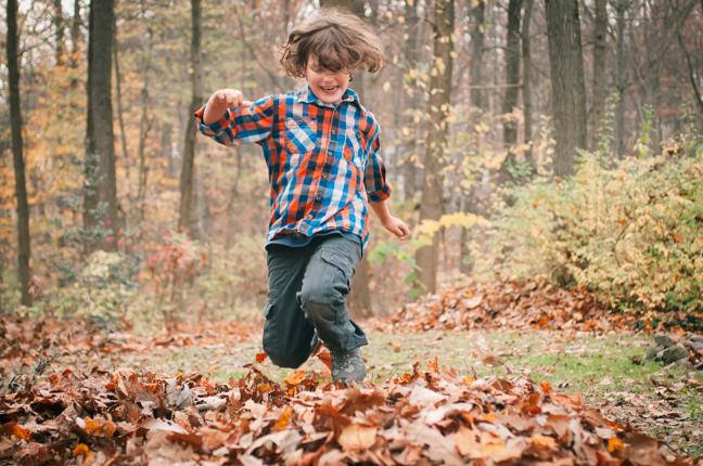 boy jumping into a pile of leaves