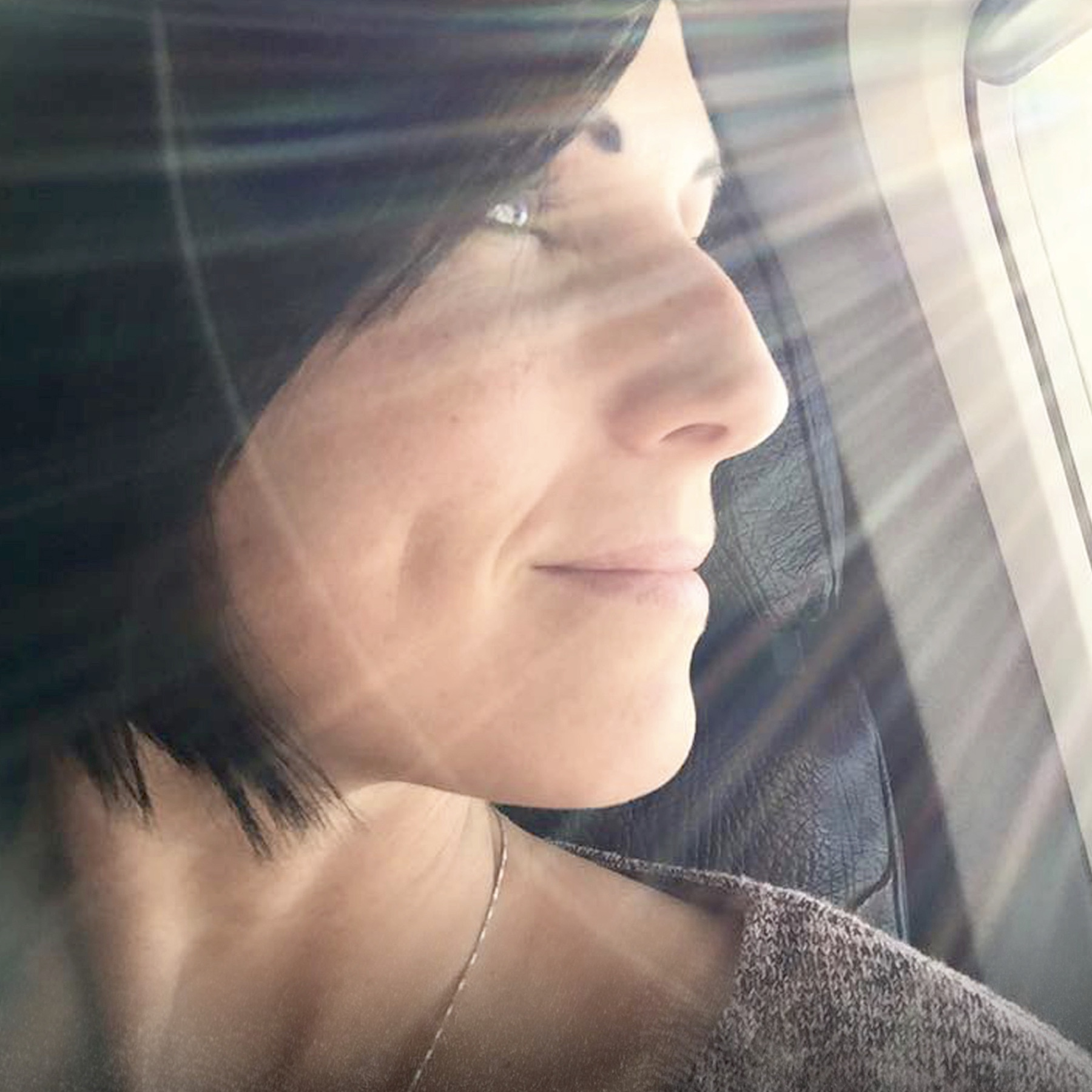 woman with brown hair gazing right out an airplane window with the sun shining in