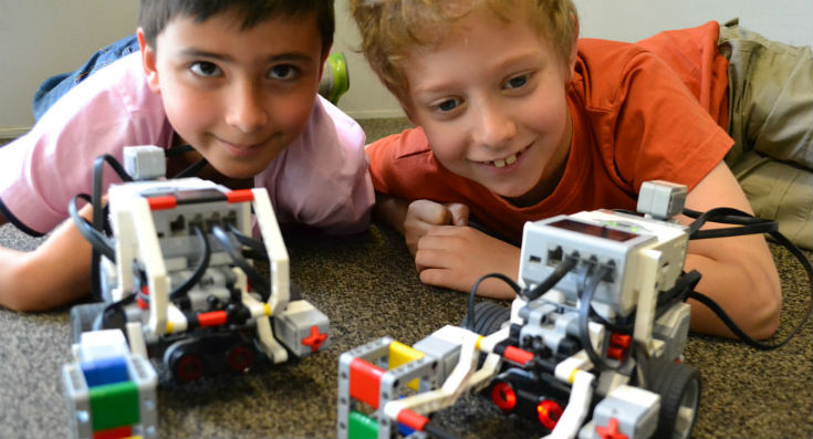 Two kids looking over two Lego robots