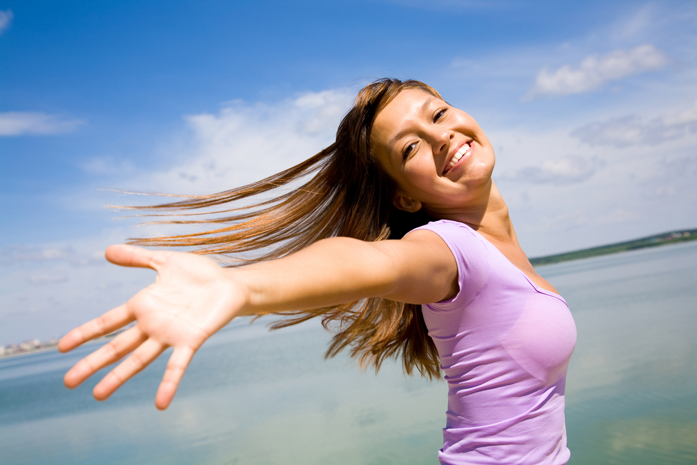 Smiling woman with open arms against a blue sky