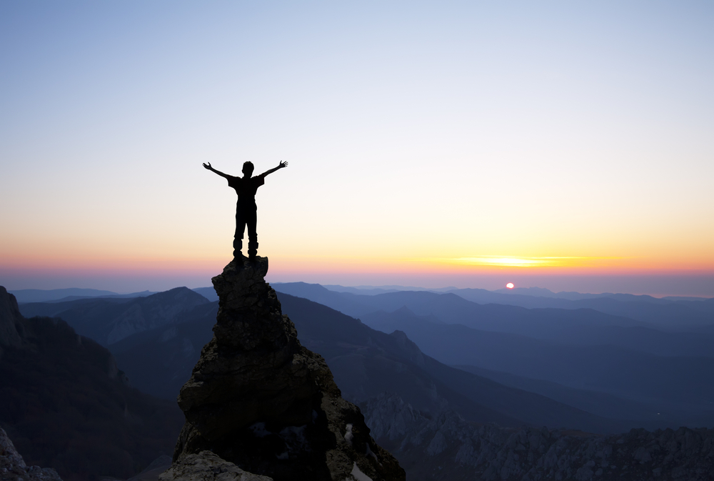 Person on mountain top at sunrise arms upraised