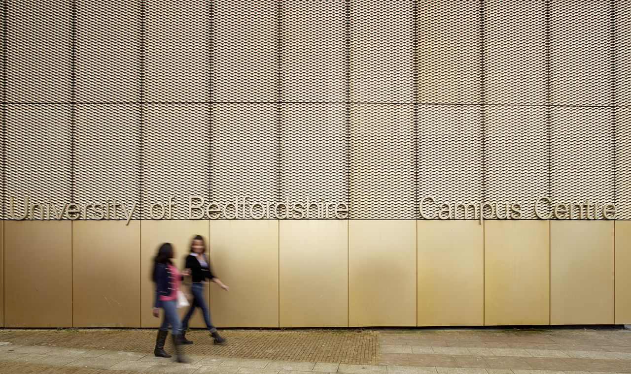 Two students walking past the main campus centre entrance to University of Bedfordshire