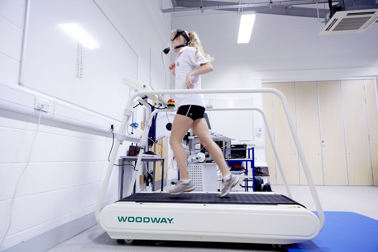 Student monitoring breathing while running on a treadmill